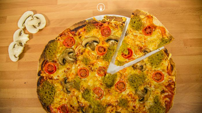 Pizza integral con mozzarella, tomate y pesto